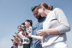 Les jeunes à l'aide des smartphones pour rechercher le réseau Images stock