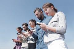 Les jeunes à l'aide des smartphones pour rechercher le réseau Photographie stock