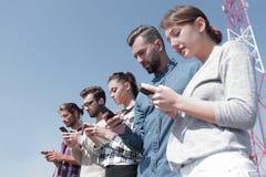 Les jeunes à l'aide des smartphones pour rechercher le réseau Photo libre de droits