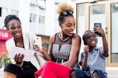 Les jeunes à l'aide des téléphones portables et des tablettes Images stock