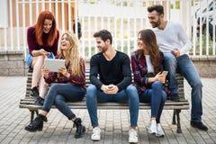Les jeunes à l'aide du smartphone et des tablettes dehors Photos libres de droits