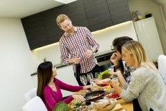 Les jeunes à la table dans la cuisine Photographie stock