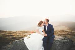 Les jeunes épousent nouvellement des couples, baisers de jeunes mariés, étreignant sur la vue parfaite des montagnes, ciel bleu Photo stock