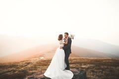 Les jeunes épousent nouvellement des couples, baisers de jeunes mariés, étreignant sur la vue parfaite des montagnes, ciel bleu Images stock