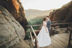 Les jeunes épousent nouvellement des couples, baisers de jeunes mariés, étreignant sur la vue parfaite des montagnes, ciel bleu Photo libre de droits