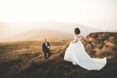 Les jeunes épousent nouvellement des couples, baisers de jeunes mariés, étreignant sur la vue parfaite des montagnes, ciel bleu Photographie stock libre de droits