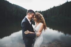 Les jeunes épousent nouvellement des couples, baisers de jeunes mariés, étreignant sur la vue parfaite des montagnes, ciel bleu Photos stock
