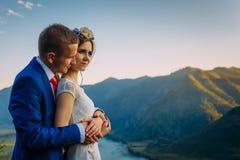 Les jeunes épousent nouvellement des couples, baisers de jeunes mariés, étreignant sur la vue parfaite des montagnes, de la ri images libres de droits