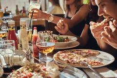 Les jeunes étudiants d'amis mangent de la pizza et des salades dans un CAM extérieur pendant la pause de midi photo libre de droits