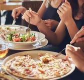 Les jeunes étudiants d'amis mangent de la pizza et des salades dans un CAM extérieur pendant la pause de midi photo stock