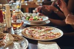 Les jeunes étudiants d'amis mangent de la pizza et des salades dans un CAM extérieur pendant la pause de midi photos stock