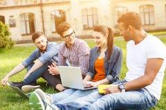 Les jeunes étudiants heureux causent dans le campus Images libres de droits
