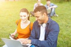 Les jeunes étudiants heureux se reposent dans la nature Photographie stock libre de droits