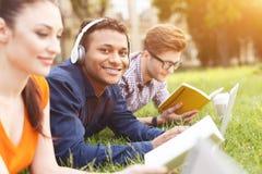 Les jeunes étudiants heureux se reposent dans la nature Images stock