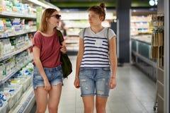 Les jeunes adolescents féminins positifs de costume ont la balade dans le supermarché, habillé dans le short de treillis et les T Image stock