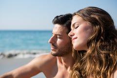 Les jeunes ajouter aux yeux ont fermé se reposer ensemble à la plage Photographie stock libre de droits