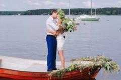 Les jeunes ajouter heureux à un bouquet et à une guirlande étreignent se reposer dans un bateau sur le fond de lac et de ciel Photos stock