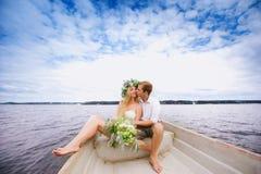 Les jeunes ajouter heureux à un bouquet et à une guirlande étreignent se reposer dans un bateau sur le fond de lac et de ciel Image libre de droits