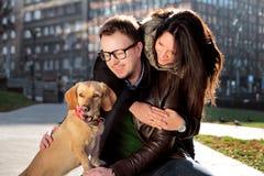 Les jeunes ajouter heureux au chien apprécient dans un beau jour Image stock