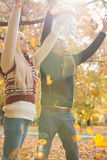 Les jeunes ajouter heureux aux bras ont soulevé apprécier les feuilles d'automne en baisse en parc Photographie stock