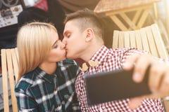 Les jeunes amants gais photographient leur baiser Image stock