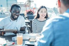 Les jeunes amicaux plaisantant tout en prenant le déjeuner ensemble Photos libres de droits