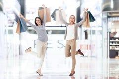 Les jeunes amies avec des paniers font des emplettes au mail Images stock