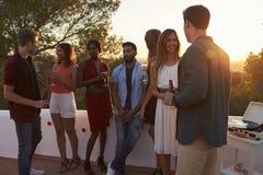 Les jeunes amis adultes parlent à une partie sur un dessus de toit au coucher du soleil Photographie stock