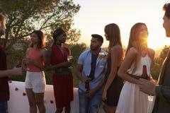 Les jeunes amis adultes parlent à une partie sur un dessus de toit au coucher du soleil Images libres de droits