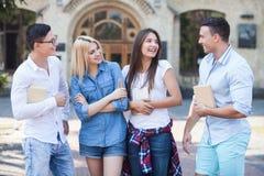 Les jeunes amis attirants parlent ensuite Photo libre de droits