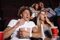 Les jeunes amis effrayés s'asseyant dans le cinéma observent le film Photographie stock