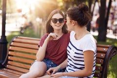 Les jeunes amis féminins positifs regarde joyeux l'un l'autre, dernières nouvelles de shre, se sont habillés en passant, recreat  Photos stock