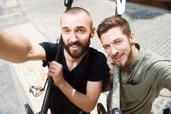 Les jeunes amis gais font le selfie dans la ville Image stock