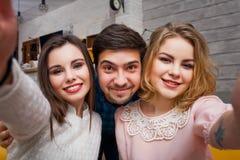 Les jeunes amis gais font le selfie dans un café Photos stock