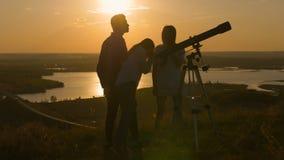Les jeunes amis heureux regarde par télescope de vue et amusement de avoir le coucher du soleil d'été Photographie stock