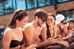 Les jeunes amis joyeux regardent des photos prises sur le smartphone dans la piscine pendant l'été Photographie stock libre de droits