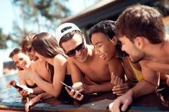 Les jeunes amis joyeux regardent des photos prises sur le smartphone dans la piscine pendant l'été Image stock