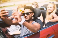 Les jeunes amis prennent un selfie dans une voiture de cabriolet Photographie stock libre de droits