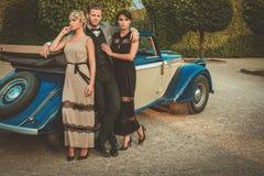 Les jeunes amis riches s'approchent du convertible classique Photo libre de droits