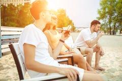 Les jeunes appréciant des vacances d'été prenant un bain de soleil le boire à la barre de plage Photographie stock