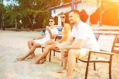 Les jeunes appréciant des vacances d'été prenant un bain de soleil le boire à la barre de plage Photo libre de droits