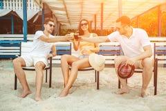 Les jeunes appréciant des vacances d'été prenant un bain de soleil le boire à la barre de plage Photo stock