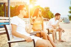 Les jeunes appréciant des vacances d'été prenant un bain de soleil le boire à la barre de plage Image stock