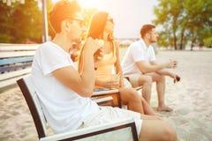 Les jeunes appréciant des vacances d'été prenant un bain de soleil le boire à la barre de plage Photos libres de droits