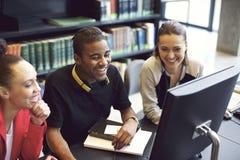 Les jeunes appréciant l'étude dans la bibliothèque Photos stock