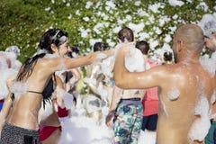 Les jeunes appréciant une mousse font la fête sur la plage Images libres de droits