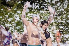 Les jeunes appréciant une mousse font la fête sur la plage Photos libres de droits