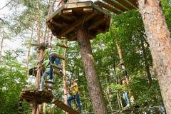 Les jeunes apprennent à s'élever dans les cordes élevées courent photo libre de droits