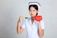 Les jeunes asiatiques soignent la seringue de prise et le coeur rouge Photo libre de droits