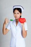 Les jeunes asiatiques soignent la seringue de prise et le coeur rouge Image stock